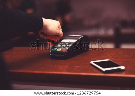 Payment with credit card. EDC machine or terminal for cashless payments near mobile phone. Male hand puts bankcard into reader on defocused background. Credit card payment and electronic bank concept