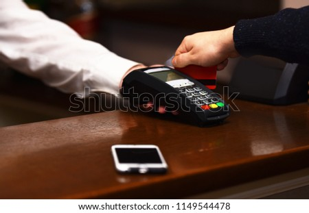 Payment with credit card. Male hand puts bankcard into reader on defocused background. Credit card terminal for cashless payments near mobile phone. Electronic finance and shopping concept.