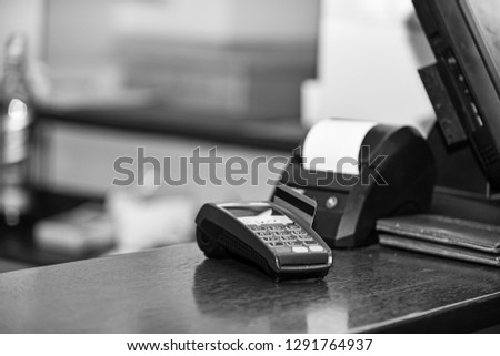 Payment with credit card. Red bankcard inserted in EDC machine on defocused background. Credit card payment and electronic bank concept. Credit card terminal for cashless payments.