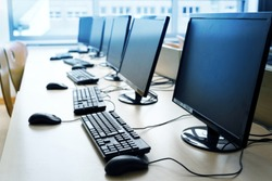 Pc computer workspaces in a row for creative workers, programmer or students in a computer lab, selected focus, narrow depth of field
