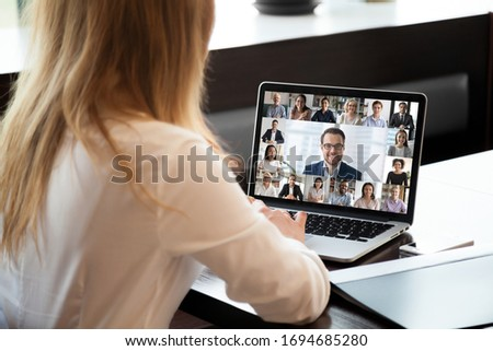 Pc screen view over woman shoulder at group video call. Visual communication between engaged diverse people distantly using webcam and laptop internet connection app. International remote chat concept