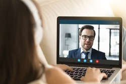 Pc screen view over woman shoulder, female wear headphones sitting on sofa make video call have distant communication using videoconference app working from home to prevent corona virus spread concept