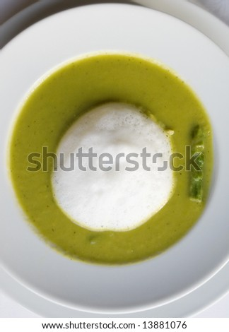 Pea soup with a green asparagus and whipped cream