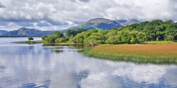 Peace and tranquillity on Lough Leane, Killarney, Ireland, with fluffy white clouds reflected in the calm lake waters.
