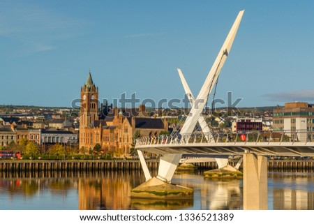 Peace bridge and guildhall in Derry Londonderry Northern Ireland with warm sunny sky
