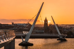 Peace bridge over the river foyle and guildhall in Derry Londonderry Northern Ireland