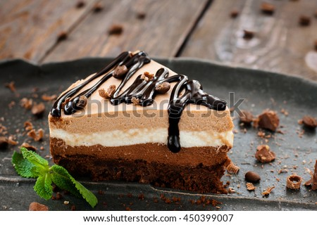Peace of layered souffle dessert with chocolate sauce on black plate with mint leaves, on blurred wooden table #450399007