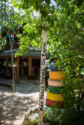 Peace pole message next to colorful stacked tires and tree in Cancun, Mexico. May the peace prevail on earth wooden pole with blurry trees and building as background. Global peaceful movement