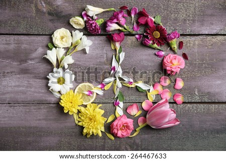 Peace symbol of beautiful flowers, on wooden table