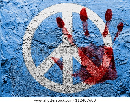 Peace symbol painted on grunge wall with bloody palmprint over it