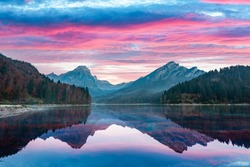 Peaceful autumn view on Obersee lake in Swiss Alps. Dramatic sunset sky and mountains reflections in clear water. Nafels village, Switzerland. Landscape photography