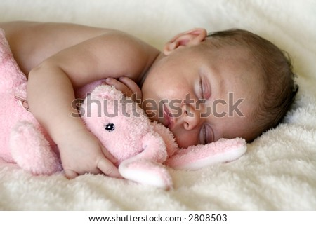 peaceful baby asleep with pink bunny rabbit