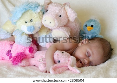 peaceful baby asleep with stuffed toys