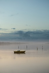 Peaceful boat alone at low tide. Fog on the horizon. Stormy sky.
