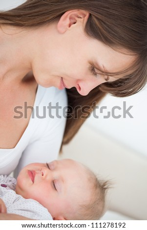 Peaceful brunette woman holding her little daughter indoors