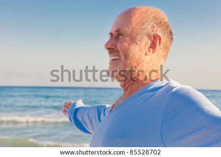 peaceful carefree older man with outstretched arms enjoying happy retirement on the coast