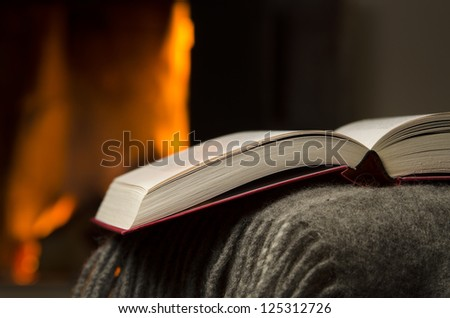 Peaceful closeup of open book resting on a arm rest of a couch. Warm fireplace on background.
