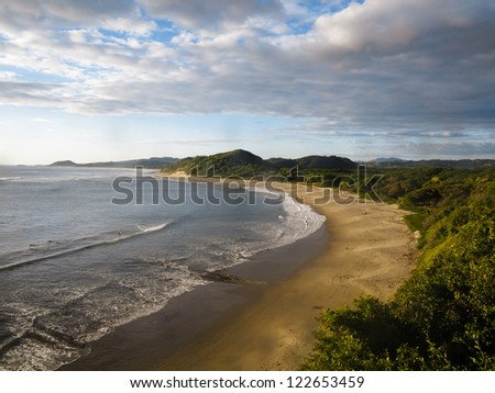 Peaceful coast line of Nicaragua with deserted sandy beach at low tide and green foliage.