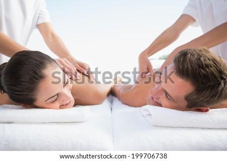 Peaceful couple enjoying couples massage poolside outside at the spa