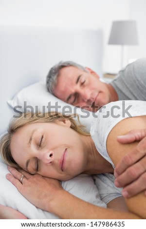 Peaceful Couple Sleeping And Spooning In Bed In Bedroom At Home