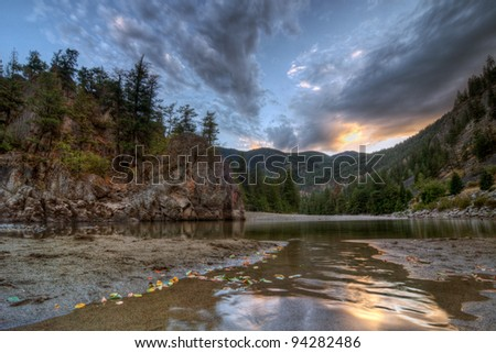 Peaceful evening at a mountain creek bend with sunset reflection
