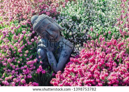 Peaceful garden. Traditional serene buddha statue ornament with beautiful flowers. Mindful serenity and nature in this calming image portraying tranquility and mindfulness in zen meditation.  #1398753782