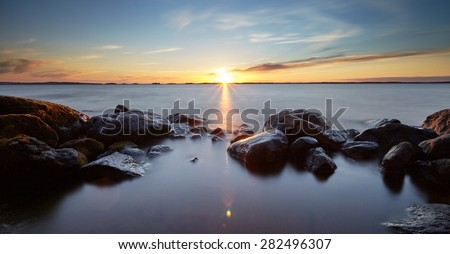 Peaceful landscape with very long exposure and sunset. Silky smooth water flows around the rocks in the water.