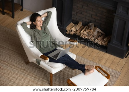 Peaceful latina woman lean back in comfy chair with hands over head take break in work with laptop relax at modern living room near fireplace. Calm young lady enjoy rest at home breath clean fresh air Foto stock ©