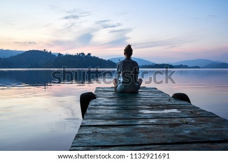 Peaceful lifestyle shot of woman sitting on dock at sunset on Lake Bunyonyi, Uganda, Africa.