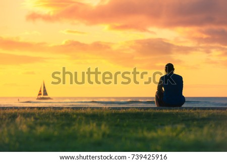 Peaceful moments. Thoughtful man sitting watching the sunset and sale boat go by.