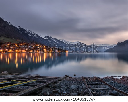 peaceful moody morning at the lake, swiss alps mountains reflecting in the water while dark clouds cover the sky #1048613969