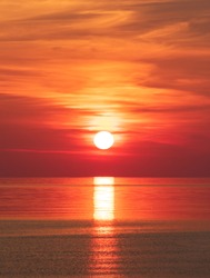 Peaceful orange red sea sunrise (vertical)