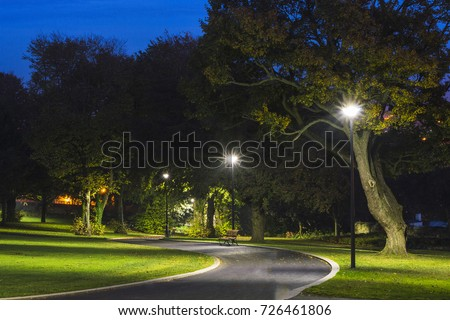 Stock Photo Peaceful Park in the Night with Street Lights, Trees, Green Grass and Pathway.