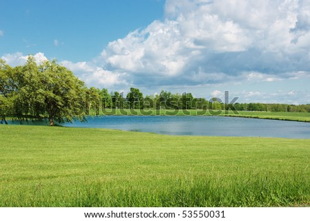 Peaceful Pond Scene.  A brilliant blue sky and massive fluffy white cumulus clouds are reflected in a farm pond that is surrounded by manicured green grass and bordered by a stand of shade trees