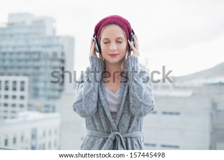Peaceful pretty blonde listening to music outdoors on urban background