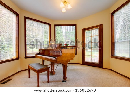 Photo of Peaceful room with antique piano and ottoman.