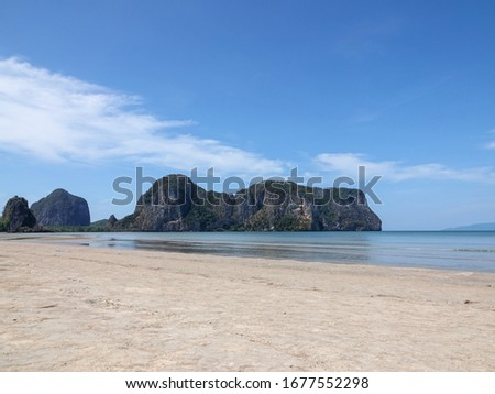 Peaceful sandy beach with mountain and blue sky at Rajamangala Beach, Trang province, southern Thailand.