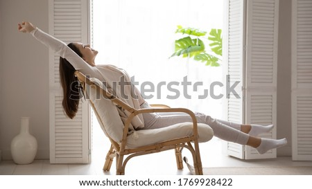 Peaceful satisfied young woman stretching in cozy armchair at home, smiling happy beautiful girl relaxing with hands and legs outstretched in chair, enjoying lazy leisure time at home, meditating