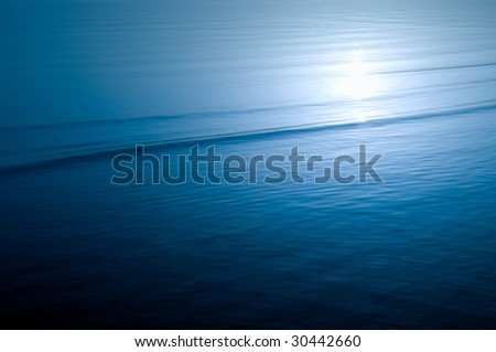 peaceful sea water surface with sunlight reflection