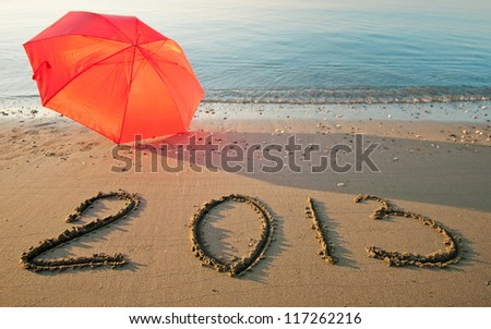 Peaceful seashore with umbrella and 2013 drawn on  sand