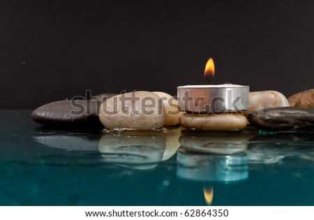 Peaceful Setting with Rocks and Candle on Water