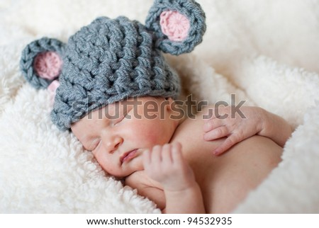 Peaceful sleeping newborn baby in a grey mouse hat