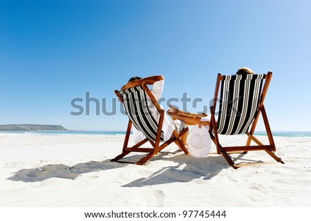 peaceful summer beach couple sitting and relaxing enjoying the sunshine on a pristine coastline - stock photo