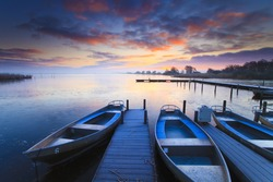 Peaceful sunrise with dramatic sky and boats and a jetty