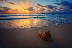 Peaceful sunrise with god rays over pristine sandy beach with a sand sculpture in the foreground