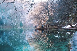 Peaceful, tranquil reflection on lake. Beautiful winter landscape at Plitvice Lakes National Park. Calming stroll in nature.