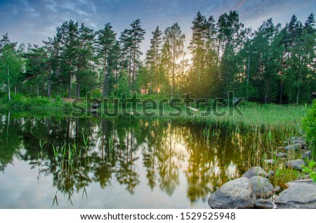 Peaceful tranquill view of dusky evening nature from a lake side with stones in the water during the summer in europe vacation