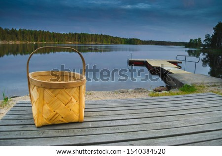 Peaceful tranquill view of nature with lonely wooden bucket sitting on an old wooden table in front of a lake during the summer in europe vacation