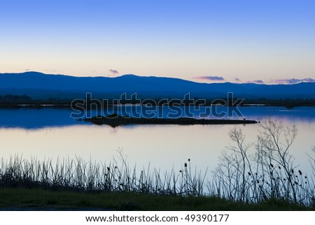 Peaceful twilight scene at the Sacramento National Wildlife Refuge in the California Central Valley with distant blue mountains and a few small pink and gray clouds on the horizon - stock photo