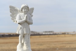 Peaceful white praying angel statue in an open field of a cemetery